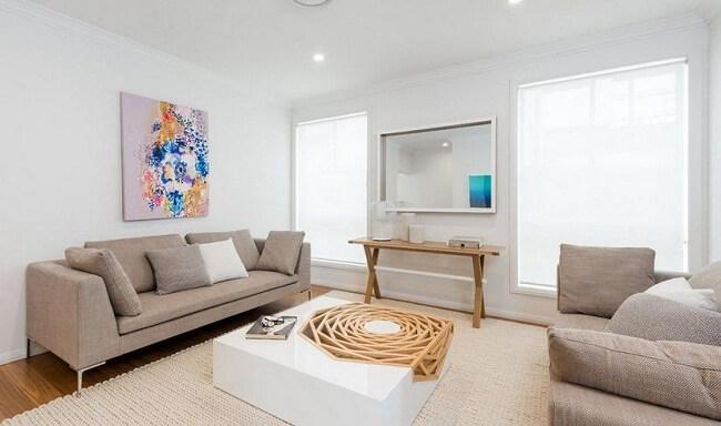 Bức tường trắng trực quan kết hợp với ánh đèn màu làm cho căn phòng rộng rãi sau khi sửa nhà này.