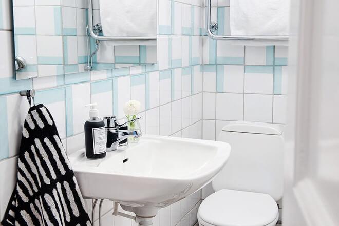 Phòng tắm sau khi cải tạo căn hộ với tông trắng, điểm xuyết màu xanh nhạt, nhà vệ sinh thiết kế đơn giản, ấn tượng trong căn hộ chung cư.