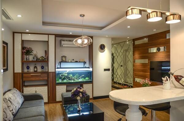 Phòng khách với gam màu trung tính, đồ nội thất gỗ sang trọng và ấm áp cho căn phòng, sau sửa chữa cải tạo căn hộ tập thể cũ.