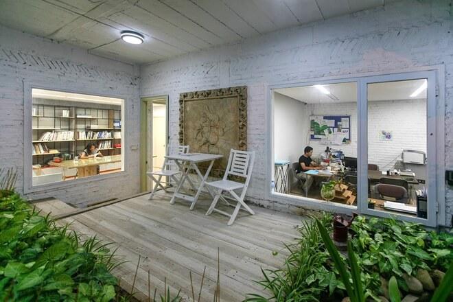 Sửa chữa cải tạo nhà với các phòng làm việc được thiết kế cửa sổ kính lớn, hướng góc nhìn ra vườn. Ở đây cũng đặt bộ bàn ghế thư giãn giữa màu xanh cây lá.
