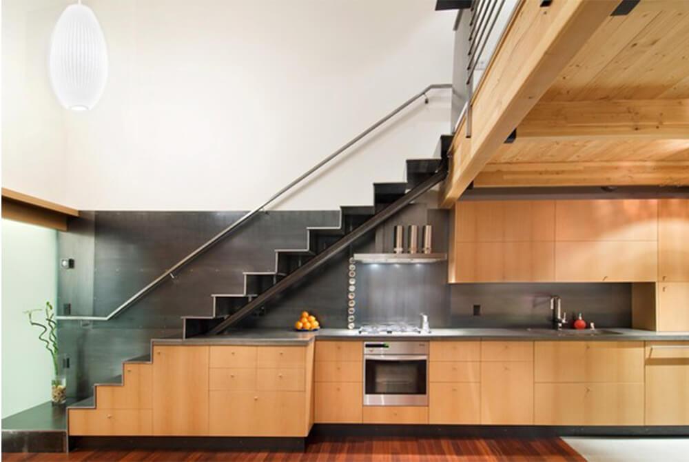 Thiết kế nhà với không gian cầu thang đơn giản, hệ tủ bếp dưới gầm thang vẫn rất hiện đại và tiện nghi.