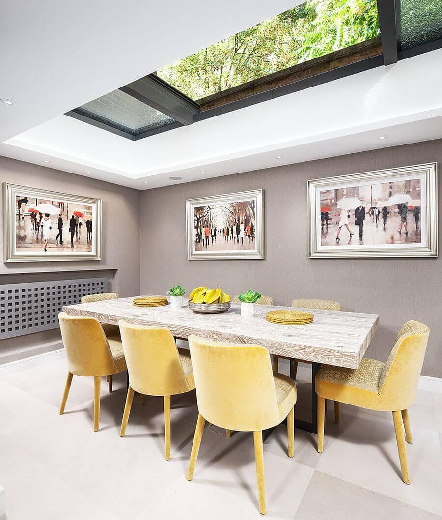 Phòng ăn với kiểu cửa giếng trời trên trần nhà, tràn ngập ánh sáng thiên nhiên, không gian phòng ăn với gam màu tường xám, trắng, kết hợp thêm chiếc ghế bọc nệm màu vàng, trong thiết kế nội thất phòng ăn này.