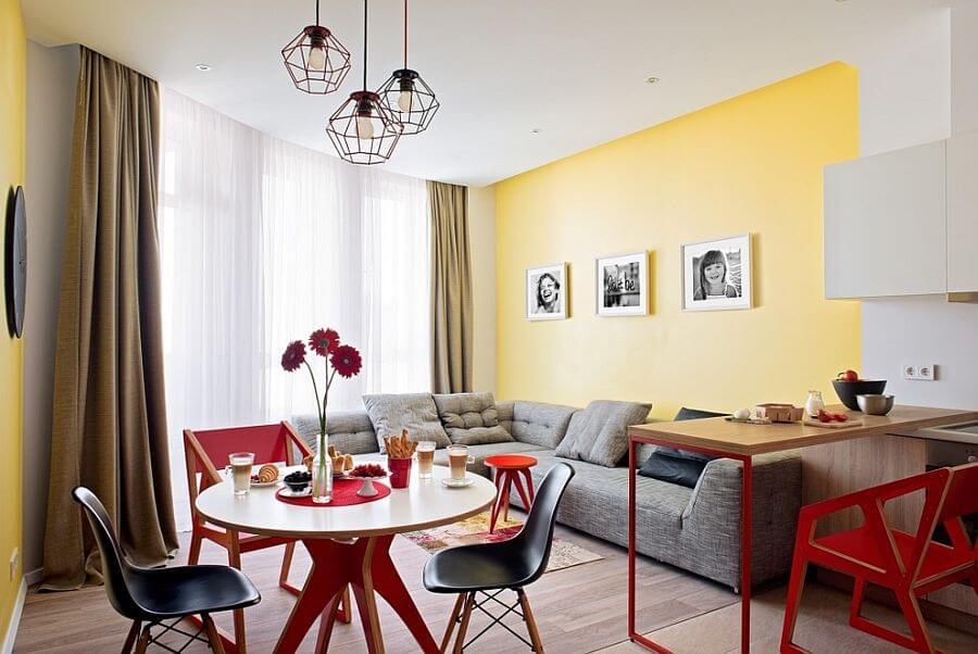 Phòng ăn và phòng khách kết nối mở thông nhau với màu vàng, trắng và màu xám, trong mẫu thiết kế nội thất phòng ăn đẹp này.