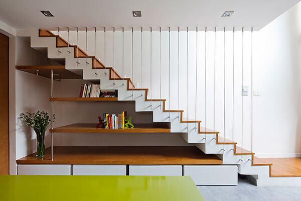 Cầu thang trong mẫu thiết kế nhà này, tinh tế và thanh mảnh trở thành mảng trang trí đẹp cho khu vực bếp ăn. Phần gầm cầu thang được tận dụng làm tủ sách, bày đồ trang trí và cất đồ.