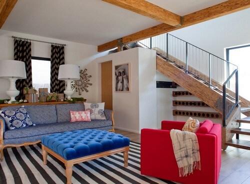Thiết kế nội thất phòng khách với tông trắng tường, mặt bàn màu xanh dương cùng ghế đôn màu đỏ tạo điểm nhấn hút mắt.