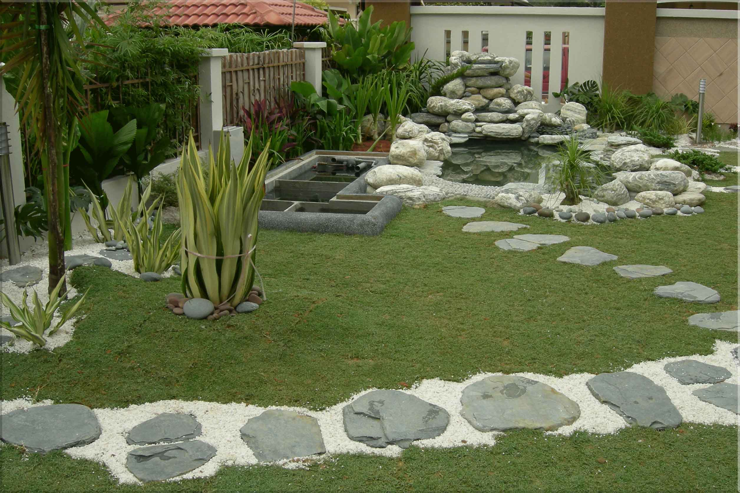 Một góc tiểu cảnh cây xanh được đặt ở sân trước, trong mẫu thiết kế nhà cấp 4 này.