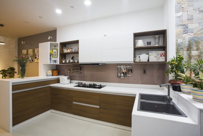 Thiết kế nhà ống với khu vực nấu nướng rộng mở, thoáng đãng nhìn ra sân nhỏ phía sau. Hệ tủ bếp lớn nhưng được thiết kế phẳng nên không tạo cảm giác nặng nề.