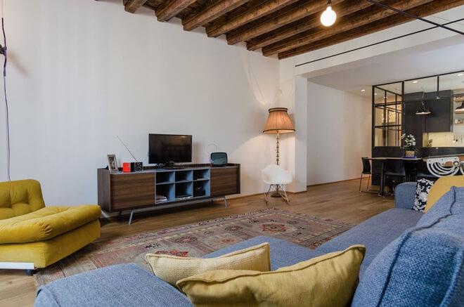 Sử dụng những thanh xà gỗ kết hợp tường màu trắng ấn tượng, sau sửa chữa phòng khách chung cư này.
