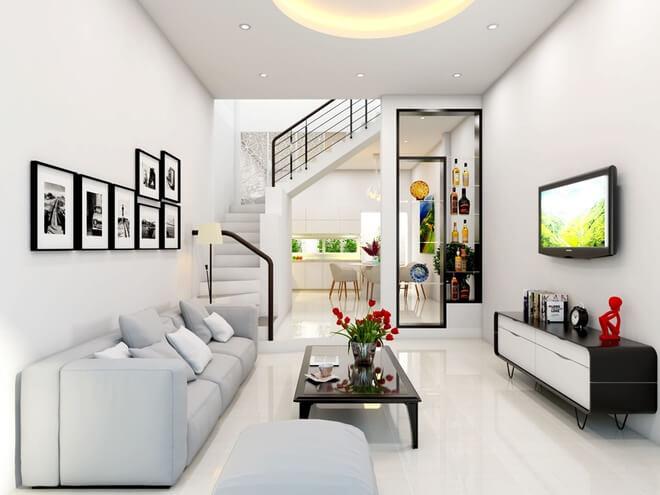 Thiết kế nhà ống,Phòng khách với tông màu trắng sáng sủa. Dàn kệ gỗ màu đen và nhữngbức tranh đen trắng tạo điểm nhấn cho không gian thêm đẹp mắt