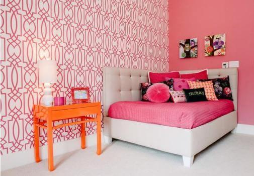 Căn phòng ngủ sơn màu hồng quyến rũ với 2 mảng tường sắc hồng. Màu ga trải và vỏ gối chính là màu hồng của bức tường có 2 bức tranh để cân bằng màu sắc.