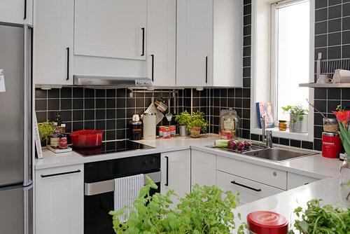 """Đen - trắng tiếp tục là cặp màu chủ đạo của phòng bếp. Xen giữa hệ tủ bếp màu trắng """"khổng lồ"""" là những chi tiết màu đen quyến rũ của gạch ốp tường"""