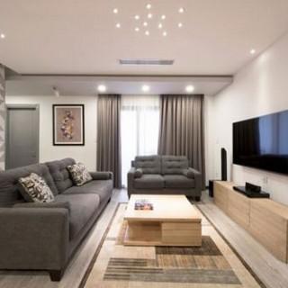 Phòng khách được thiết kế cải tạo căn hộ sang trọng với gam màu trầm