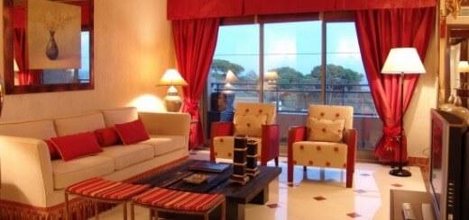 Phòng khách sơn nhà màu cam chủ đạo, kết hợp rèm và những họa tiết khác màu đỏ rất ấn tượng cho căn phòng.