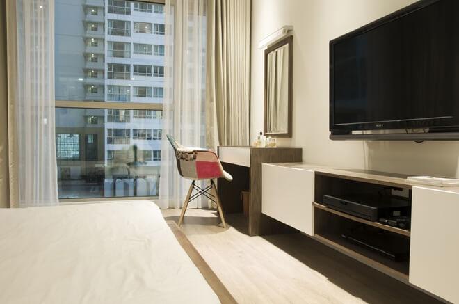 Phòng ngủ chính sử dụng tủ đồ và giường có thiết kế gọn gàng tạo cảm giác nhà rộng thoáng hơn sau khi cải tạo căn hộ chung cư.