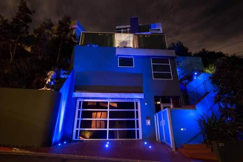 Mẫu thiết kế nhà cao 4 tầng, 1 tum và tỏa ra ánh sáng xanh mờ ảo vào ban đêm.