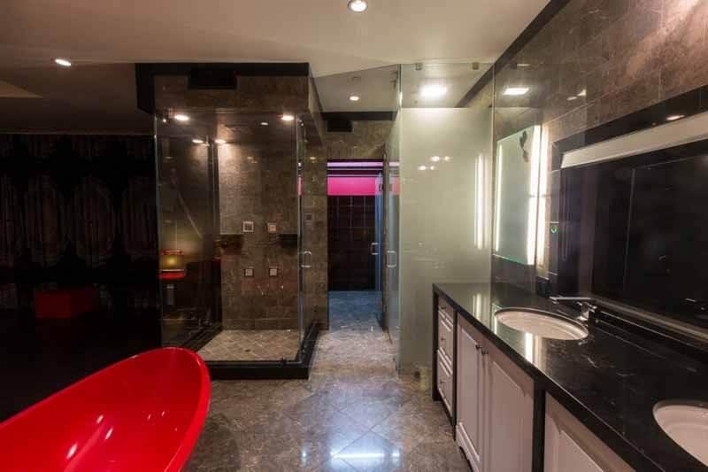 Cặp màu đỏ-đen thống trị trong phòng tắm với tâm điểm là chiếc bồn tắm màu đỏ, đầy cá tính trong mẫu thiết kế nhà.