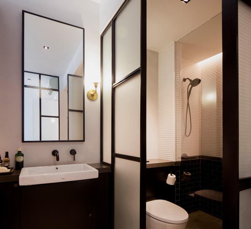 Phòng tắm rộng rãi với khu vệ sinh và khu rửa tách biệt, với màu sơn nhà đen-trắng