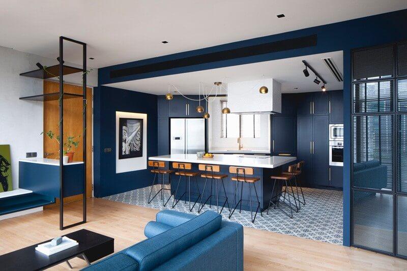 Phòng khách được thiết kế ngay bên cạnh bếp, căn phòng rộng với điểm nhấn là chiếc ghế sofa màu xanh nổi bật.