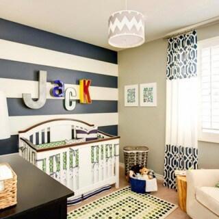 Cách sơn phòng ngủ cho bé với những đường kẻ ngang màu xanh và trắng theo phong cách hải quân tạo ra một bức tường nổi bật trong căn phòng của các bé trai.