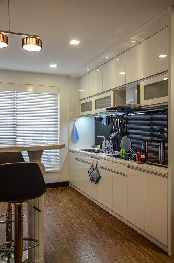 Không gian bếp gọn gàng, sạch sẽ tông màu trắng, kết hợp sàn gỗ nâu, vừa đẹp, vừa sang trong căn hộ sửa chữa cải tạo.