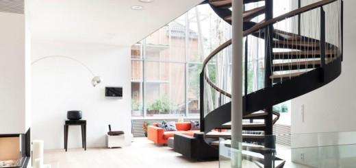 Phòng khách với cầu thang hình xoắn được bố trí cuối góc nhà tinh tế, hiện đại, trong mẫu thiết kế nhà ống 2 tầng này.