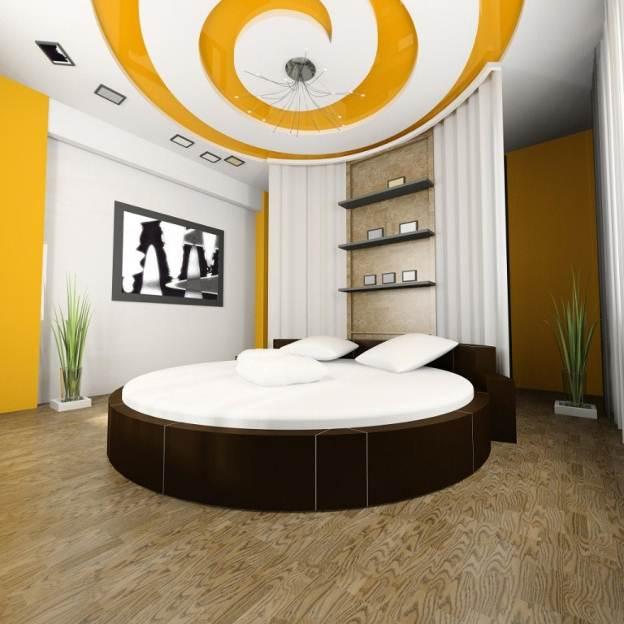 Phòng ngủ trần thạch cao giật cấp xoắn ốc với gam màu vàng nổi bật, ấn tượng.