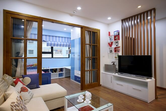 Cải tạo nhà chung cư với giải pháp chia phòng khách hiện trạng thành phòng ngủ cho em bé và phòng khách mới. Ngăn cách giữa hai khu vực này là cửa kính giúp ánh sáng tự nhiên vẫn chiếu được tới không gian sinh hoạt chung.