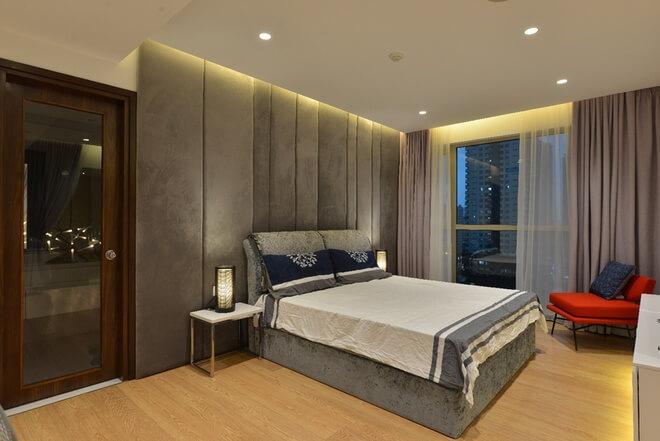 Phòng ngủ Bố mẹ sử dụng tông ghi xám kết hợp với ghế đỏ tạo điểm nhấn cho không gian ấm áp, sang trọng trong thiết kế nội thất nhà chung cư 2 tầng này.