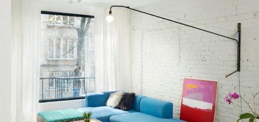 Phòng khách khá rộng sắp xếp được nhiều thứ. Một bộ ghế sofa màu xanh dương được đặt sát bức tường gạch sau khi cải tạo nhà, được sơn màu trắng.