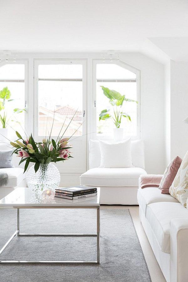 Thiết kế nội thất nhà chung cư với phòng khách trang nhã với bộ sofa trắng, điểm màu hồng pastel của gối tựa hay hoa tươi khiến không gian trở nên sinh động.