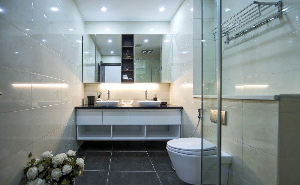 Cải tạo sửa chữa nhà chung cư với phòng tắm bố trí nội thất với tấm gương trên bồn rửa bồn tắm chính là cánh cửa mở ra một khu vực lưu trữ kín đáo.