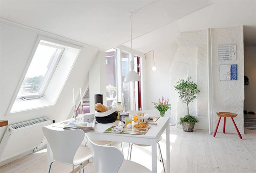 Không gian bếp, hệ tủ bếp sát tường tiết kiệm diện tích, bàn ăn sử dụng màu trắng khiến không gian bừng sáng, trong mẫu thiết kế nội thất nhà 30m2 này.