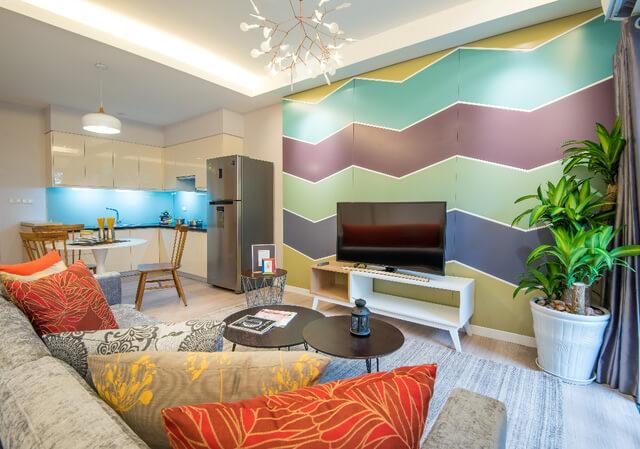 Đặc biệt, điểm nhấn của nhà chung cư này, màu sắc rực rỡ từ gối tựa và hoa văn tường khiến phòng khách trở nên sinh động và đáng yêu.