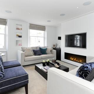 Phòng khách này, ngoài chiếc bàn kính màu đen, tường nhà và ghế sofa màu trắng, chủ nhà còn chọn thêm những gam màu như ghi nhạt, xanh hải quân, xám để bổ sung cho căn phòng.