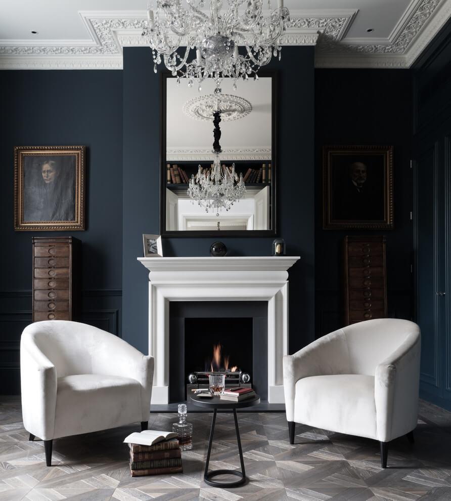 Phòng khách này có sự kết hợp của gam màu sơn tường xanh hải quân, gạch lát sàn màu ghi xám kẻ zic zac, kết hợp thêm chút màu đen ở viền gương và chiếc bàn nhỏ, hai chiếc ghế tựa sofa màu trắng giúp phòng khách có thêm sự đa dạng về màu sắc mà vẫn giữ được phong cách đơn sắc cho gian phòng.