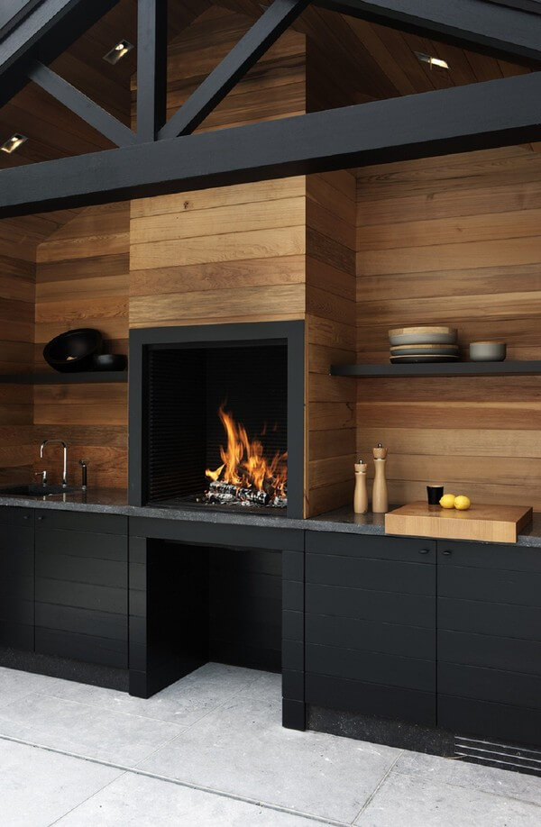 Toàn bộ tường của nhà bếp này đều được ốp gỗ từ những thanh gỗ dài, phần tủ đã được sơn đen lại. Kết hợp cùng nền gạch màu xám tạo nên nét hiện đại vô cùng cuốn hút.